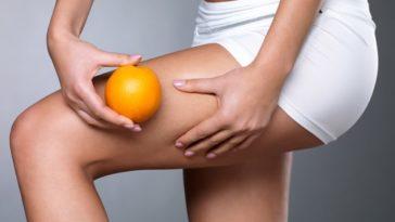 mujer-rosando-su-pierna-y-sosteniendo-una-naranja